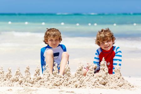 Two kid boys building sand castle on tropical beach of Playa del Carmen, Mexico