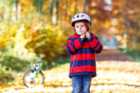 Active child putting safe helmet before cycling on sunny fall day in nature. Stock Photo - 107450628