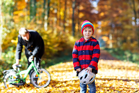 Little kid boy of five years and his father in autumn forest with a bicycle. Active child putting his bike helmet. Safety, sports, leisure with kids concept. Man with bike on background. Stock Photo