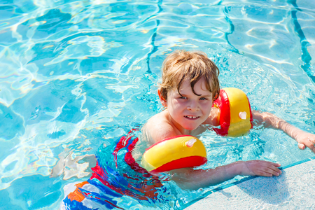Happy little kid boy having fun in an swimming pool. Active happy child learning to swim. with safe floaties or swimmies. Family, vacations, summer concept