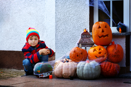 Adorable cute little kid boy sitting with traditional jack-o-lanterns pumpkins for halloween by the decorated scary door, outdoors. Child having fun and celebrating holiday Banco de Imagens