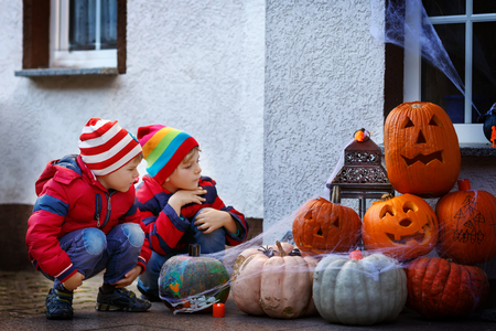 Two little kid boys sitting with traditional jack-o-lanterns pumpkins for halloween by the decorated scary door, outdoors. Children having fun and celebrating holiday Banco de Imagens