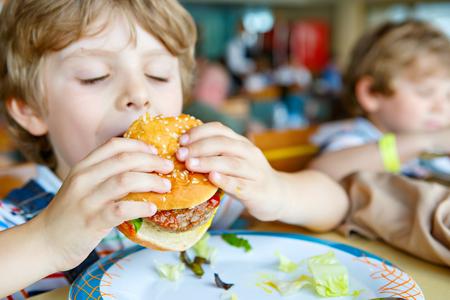 Cute healthy preschool kid boy eats hamburger sitting in school or nursery cafe. Happy child eating healthy organic and vegan food in restaurant. Childhood, health concept. Stock Photo