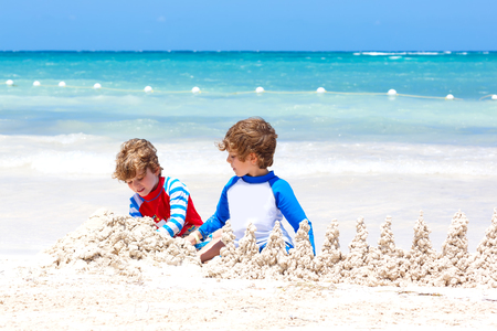 Two little kids boys having fun with building a sand castle on tropical beach of Playa del Carmen, Mexico. children playing together on their vacations Twins, Happy brothers laughing and smiling. Stock Photo