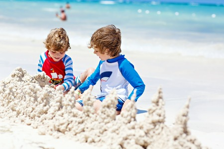 Two little kids boys having fun with building a sand castle on tropical beach of Bora Bora. children playing together on their vacations Twins, Happy brothers laughing and smiling.