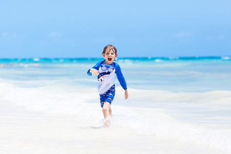 Adorable little blond kid boy having fun on tropical beach of Maldives. Excited child playing and surfing in sun protected swimsuit in ocean on vacations. White sand, Kid holding flippers for swimming. Stock Photo