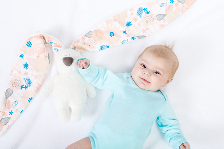 Close-up of adorable cute newborn baby girl of two months on white background. Lovely child playing with plush rabbit toy wigh bit long ears. Holiday, Easter, childhood concept