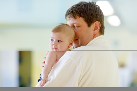 Young father and his little cute newborn baby daughter together in spa hotel. Dad in white bathrobe holding child, adorable girl on arms. Family relaxing in indoors swimming pool with baby massage Stock Photo