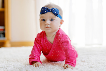 Baby girl with blue eyes lying on belly. Nursery for children. Textile and bedding for kids. Happy cute new born girl. child with headband.