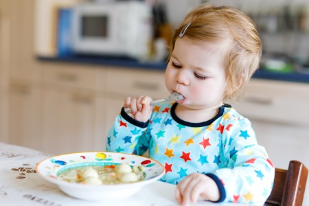 Adorable baby girl eating from spoon vegetable noodle soup. food, child, feeding and development concept. Cute toddler, daughter with spoon sitting in highchair and learning to eat by itself. Stock Photo