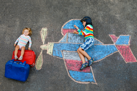 Two little children, kid boy and toddler girl having fun with with airplane picture drawing with colorful chalks on asphalt. Siblings painting with chalk and going on vacations. Archivio Fotografico