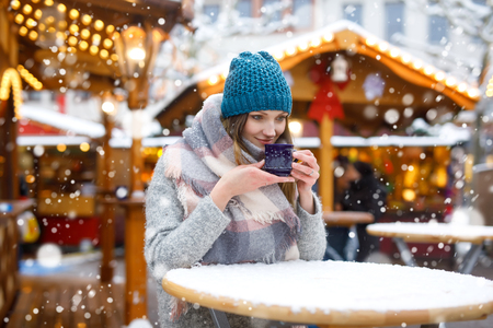 Beautiful young woman drinking hot punch, mulled wine on German Christmas market. Happy girl in winter clothes with lights on background on winter snow day in Munich, Germany. Standard-Bild