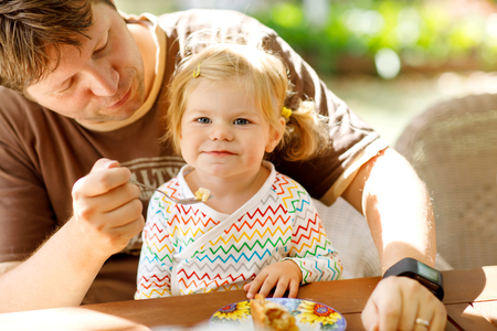 Young middle-aged father feeding cute little toddler girl in restaurant. Adorable baby child learning eating from spoon. Happy healthy family in an outdoor cafe in summer time, eating cake