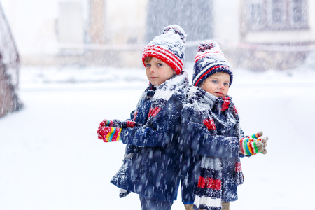 Two little kid boys in colorful fashion clothes playing outdoors during strong snowfall. Active leisure with children in winter on cold days. Happy siblings and twins having fun with first snow. Zdjęcie Seryjne