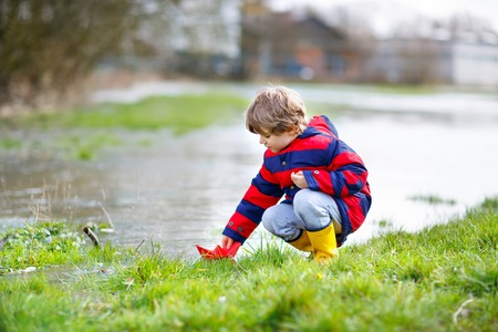 Happy little kid boy in yellow rain boots playing with paper ship boat by huge puddle on spring or autumn day. Active leisure for children. Funny child having fun outdoors, wearing colorful clothes. Stock Photo