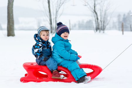 Two kid boys having fun sleigh ride during snowfall. Children sledding on snow. siblings riding a sledge. Twins play outdoors. Cute little toddlers sled on winter day. Active fun for family vacation Reklamní fotografie