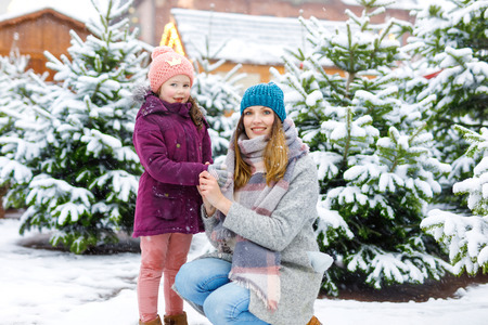 Cute little smiling kid girl and mother on christmas tree market. Happy child, daughter and young woman in winter clothes choosing xmas tree on xmas market with lights on background on winter snow day Stock Photo