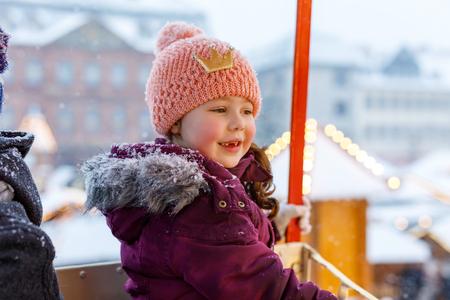 Little cute kid girl having fun on ferris wheel on traditional German Christmas market during strong snowfall.