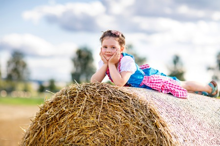 Cute little kid girl in traditional Bavarian costume in wheat field. German child with hay bale during Oktoberfest in Munich. Preschool girl play at hay bales during summer harvest time in Germany. Standard-Bild - 107874747