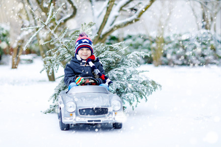 Funny little smiling kid boy driving toy car with Christmas tree. Stock Photo