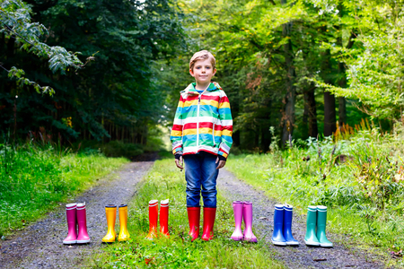 Little kid boy and group of colorful rain boots. Blond child standing in autumn forest. Close-up of schoolkid and different rubber boots. Footwear and fashion for rainy fall Reklamní fotografie