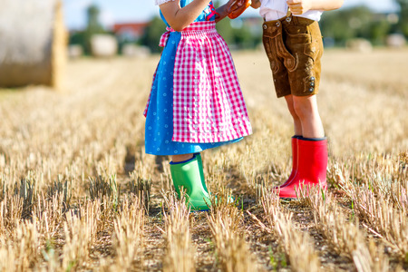 Two kids in traditional Bavarian costumes and red and green rubb Standard-Bild - 108199227