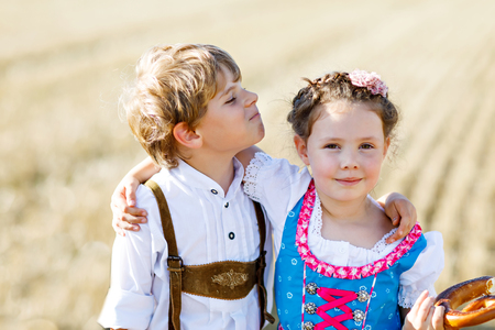 Two kids, boy and girl in traditional Bavarian costumes in wheat field Фото со стока