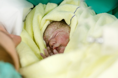 Newborn baby wrapped in blankets after birth. Mother looking for the first time on new born daughter