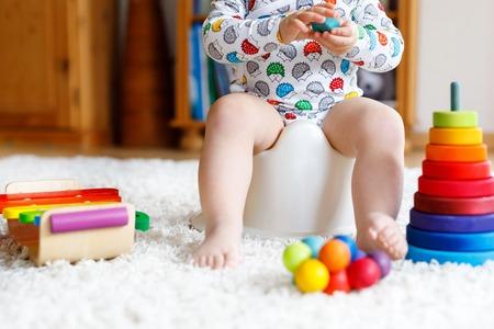 Primer plano de un lindo niño de 12 meses de edad, niña bebé sentado en el orinal. Foto de archivo