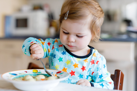 Adorable baby girl eating from spoon vegetable noodle soup. food, child, feeding and people concept 写真素材