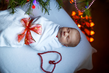 One week old newborn baby wrapped in blanket near Christmas tree Archivio Fotografico - 108206817