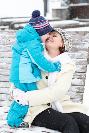 Young mother with toddler boy sitting on bench in winter park. Woman playing and hugging with cute baby son. Stock Photo