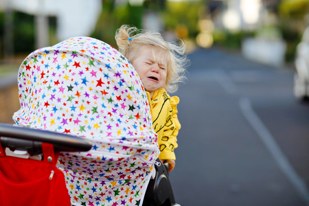 Portrait of little sad toddler girl sitting in stroller and going for a walk. Crying baby child does not want sitting in pram. Healthy daughter. Hysteric crisis of two years phase Stock Photo