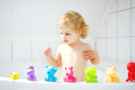 Adorable cute little toddler girl taking bath in bathtub. Happy healthy baby child playing with rubber gum toys and having fun. Washing, cleaning, hygiene for children. Standard-Bild - 108292729