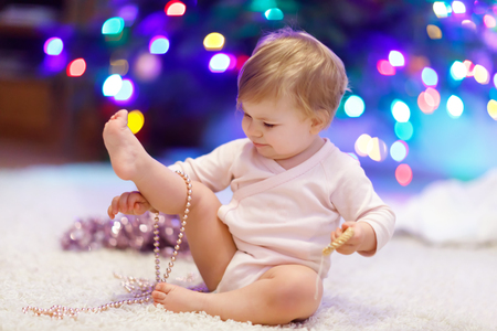Adorable baby girl holding colorful lights garland in cute hands. Little child in festive clothes decorating Christmas tree
