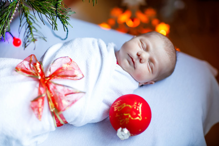 One week old newborn baby wrapped in blanket near Christmas tree Archivio Fotografico - 109263446