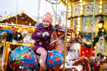 Adorable little kid girl riding on a carousel horse at Christmas funfair or market, outdoors. Stok Fotoğraf - 109263455