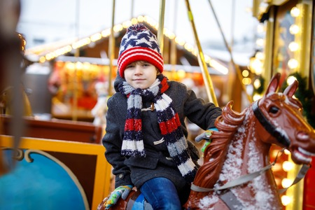 Adorable little kid boy riding on a carousel horse at Christmas funfair or market, outdoors.