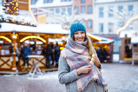 Beautiful young woman eating white chocolate covered fruits on skewer on traditional German Christmas market