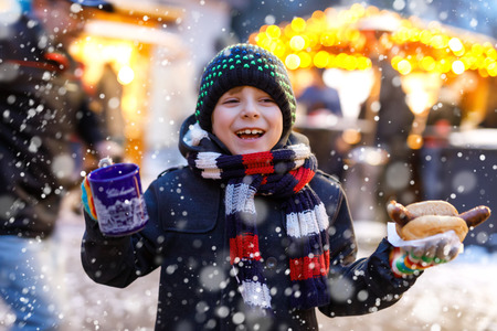 Little cute kid boy eating German sausage and drinking hot children punch on Christmas market Stock Photo