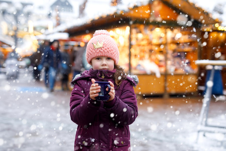 Little kid girl with hot chocolate on Christmas market Foto de archivo