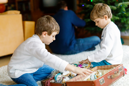 Two little kid boys decorating Christmas tree with old vintage toys and balls. Father on background