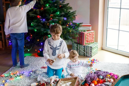 Two little kid boys and adorable baby girl decorating Christmas tree with old vintage toys and balls.