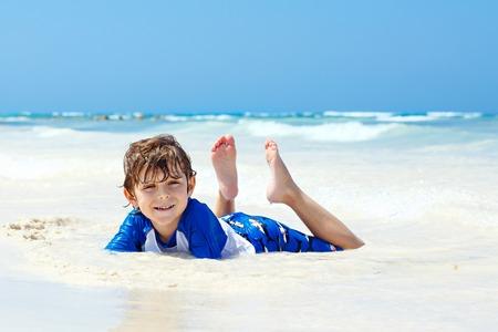 little blond kid boy having fun on tropical beach of Seychelles Stock Photo