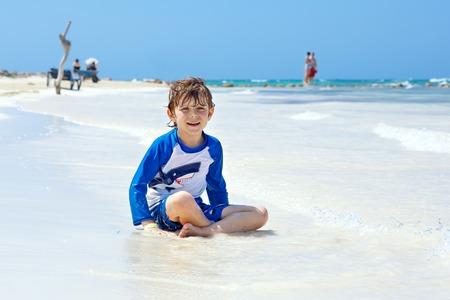 little blond kid boy having fun on tropical beach of Boracay