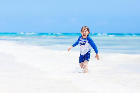 little blond kid boy having fun on tropical beach of Maldives