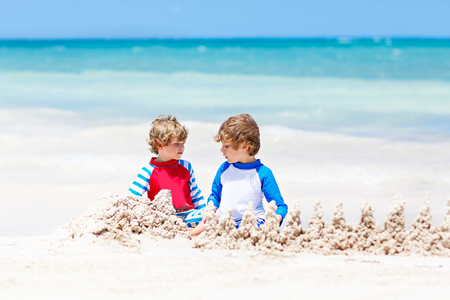 Two kid boys building sand castle on tropical beach of Tulum, Mexico Stock Photo