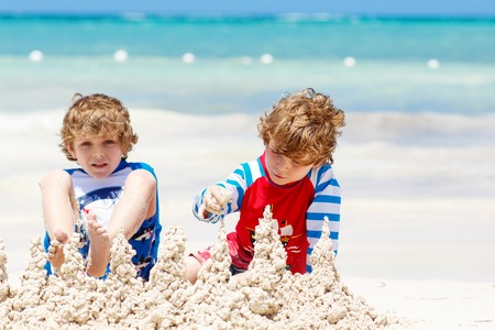 Two kid boys building sand castle on tropical beach of Maldives Stock Photo