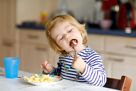 Adorable baby girl eating from spoon noodle, pasta macaroni. Cute healthy toddler child, daughter with spoon sitting in highchair and learning to eat by itself in domestic kitchen or nursery