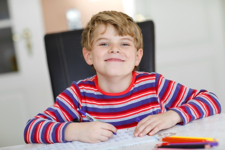 Happy smiling little kid boy at home making homework at the morning before the school starts. Little child doing excercise, indoors. Elementary school and education: Boy writing letters and numbers. Reklamní fotografie